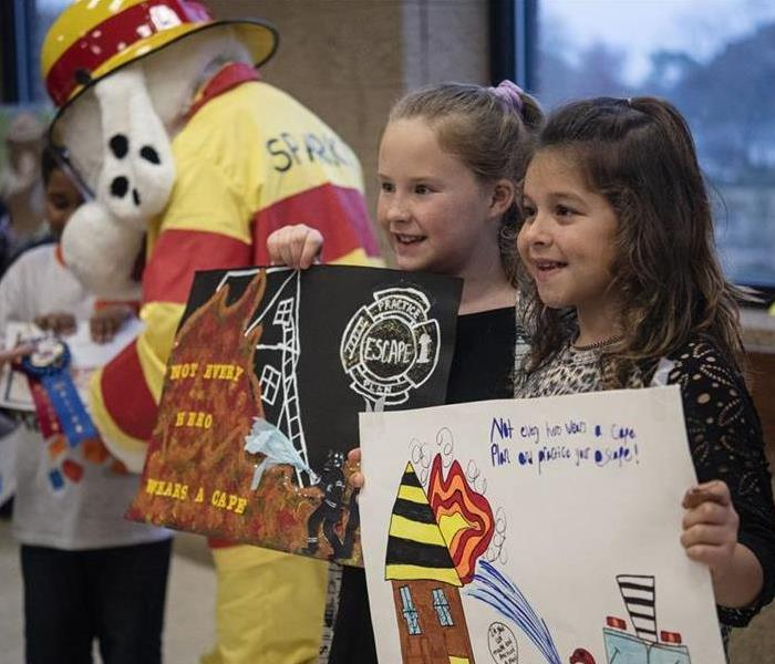 Two Young girls smiling for camera and holding up winning posters with large dog mascot in fire fighter uniform in background